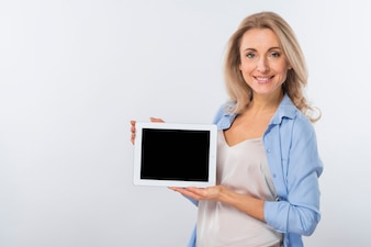 Portrait of a smiling young woman showing digital tablet against white background