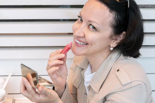 彼女の唇を描いているカフェの夏のベランダに座っている笑顔の若い女性の肖像画。