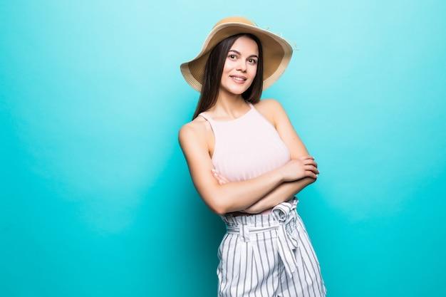 腕を組んで立って、青い壁に隔離されたコピースペースを見ている笑顔の若い女性の肖像画。