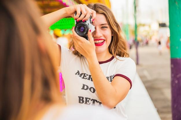 Портрет улыбающейся молодой женщины, сфотографировать ее друга