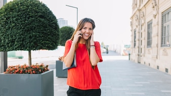 Portrait of a smiling young woman talking on cellphone