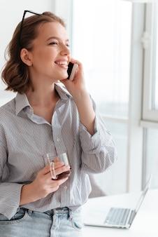 携帯電話で話している笑顔の若い女性の肖像画