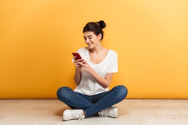 携帯電話を使用して笑顔の若い女性の肖像画