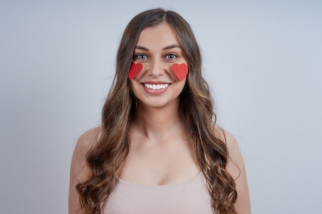 彼女の頬に接着された赤いハートを持つ笑顔の若い女性の肖像画。幸せなバレンタインデー。