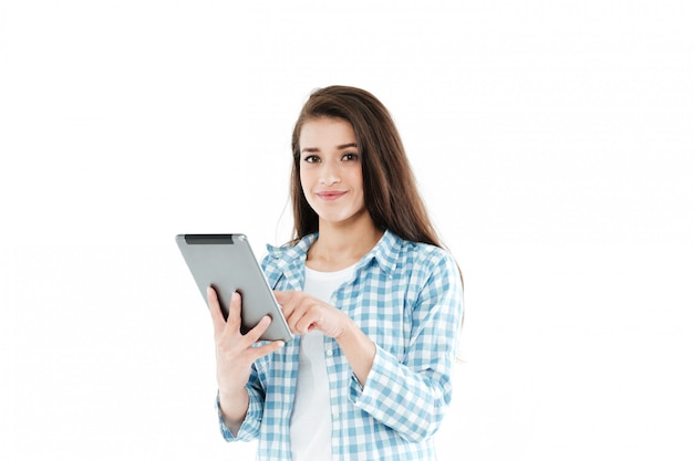 Портрет улыбающейся молодой женщины с помощью планшетного компьютера