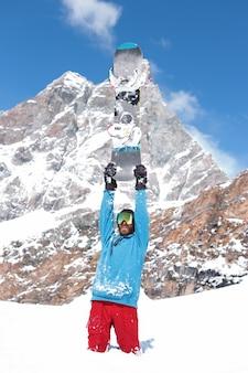 Портрет сноубордиста, поднимающего руки вверх, держа сноуборд на вершине холма