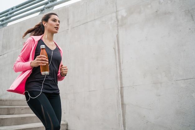 屋外の階段で走っているスポーツの女性の肖像画。フィットネス、スポーツ、健康的なライフスタイルのコンセプト。