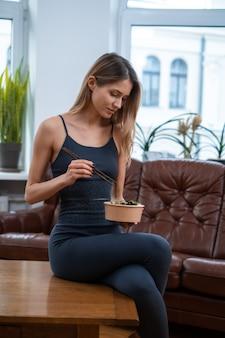 彼女は棒でサラダを食べ、窓の背景にあるリビングルームのテーブルに座っているスポーティーで美しい女性の肖像画。