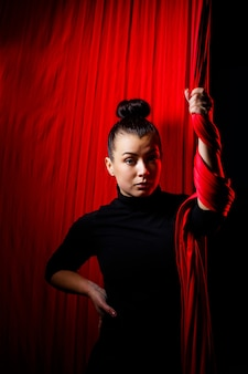 공중 체조를 위한 붉은 옷을 배경으로 한 스포츠 소녀의 초상화. 어두운 배경에서 스튜디오 촬영,