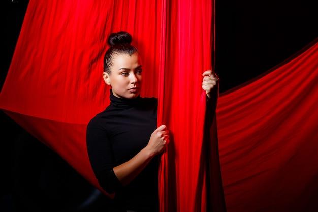 空中体操用の赤い布を背景にしたスポーツガールの肖像画。暗い背景でのスタジオ撮影、