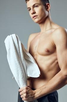 ポーズをとっているスポーツの男の裸の胴体タオルの肖像画