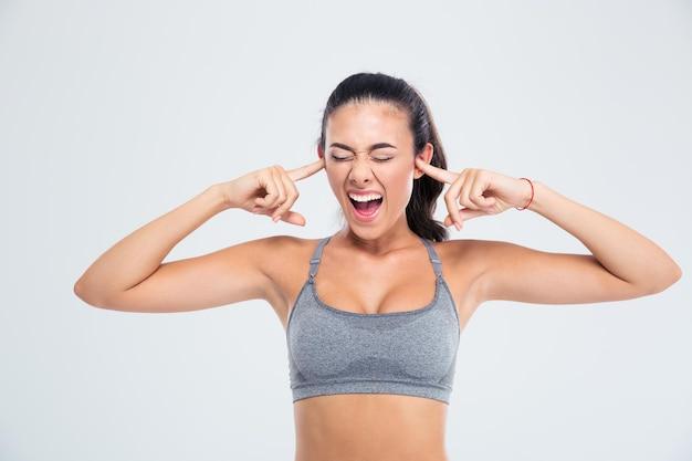 Портрет спортивной женщины, закрывающей уши пальцами и кричащей, изолированной на белой стене