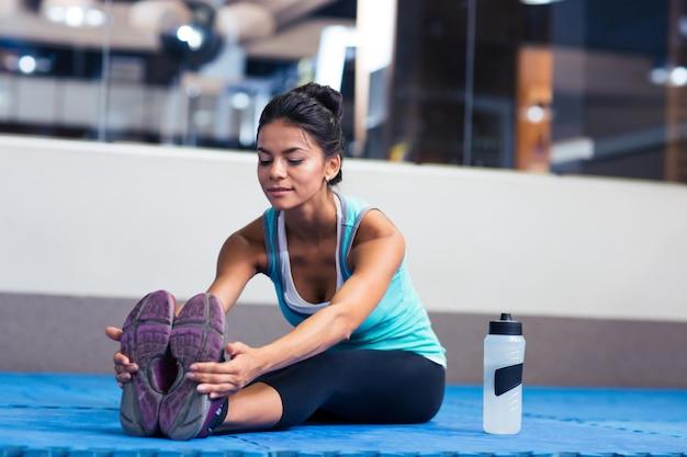 Портрет спортивной женщины, растягивающейся в тренажерном зале