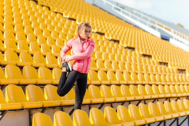 경기장에서 다리를 스트레칭 스포츠 여자의 초상화