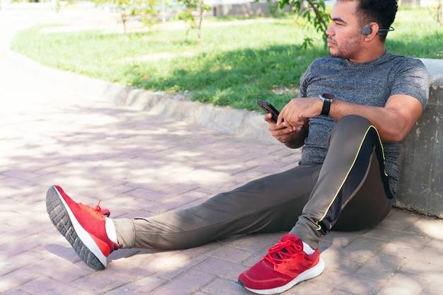 휴대 전화를 들고 공원에 앉아있는 동안 헤드폰으로 음악을 듣고 스포츠맨의 초상화.