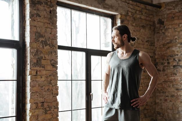 Портрет спортсмена отдыхая пока смотрящ окно
