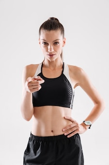 Портрет спортсменки, стоя и указывая пальцем