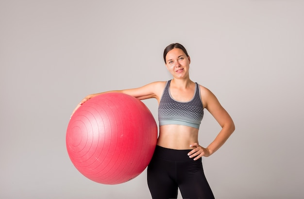 Портрет спортивной девушки с фитнес-мячом на белом с копией пространства