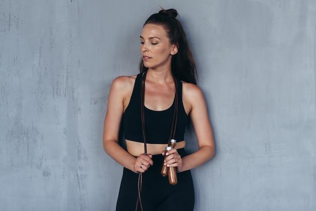 Портрет спортивной девушки со скакалкой, стоящей у стены.