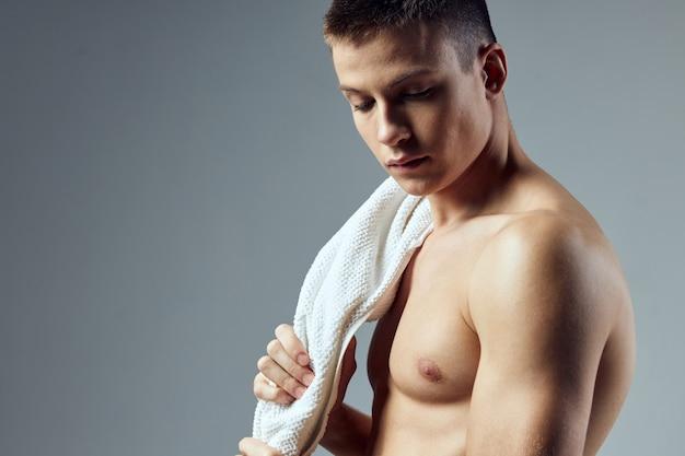 Портрет спортивного мужчины накачал полотенце крупным планом в тренажерном зале