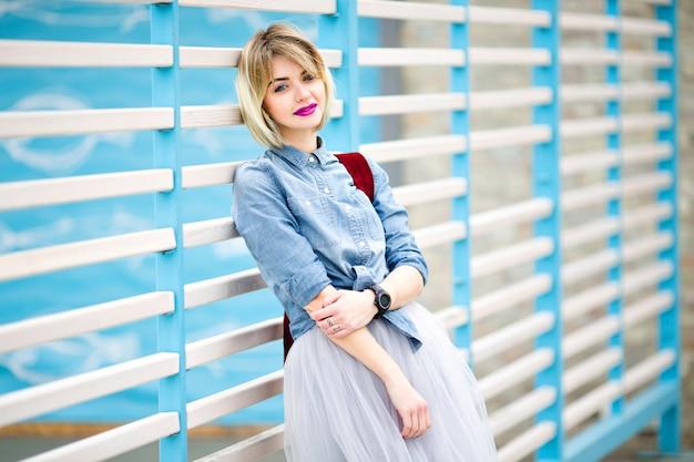青と白のストライプフェンスに寄りかかって短いブロンドの髪、明るいピンクの唇、ヌードメイクアップで立っている笑顔の女性の肖像画