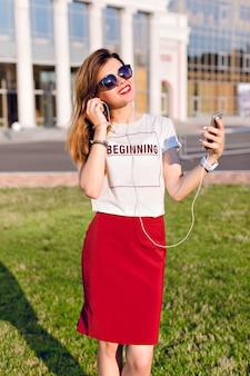 Портрет стоящей улыбающейся молодой девушки, держащей смартфон и слушающей музыку в наушниках