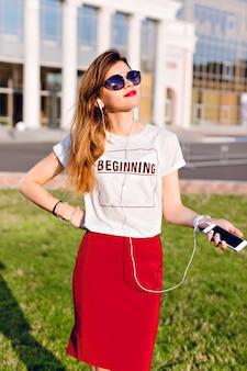 Портрет стоящей молодой девушки, держащей смартфон и слушающей музыку в наушниках