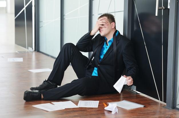 オフィスで一人で座っているストレスを感じている失望したビジネスマンの肖像