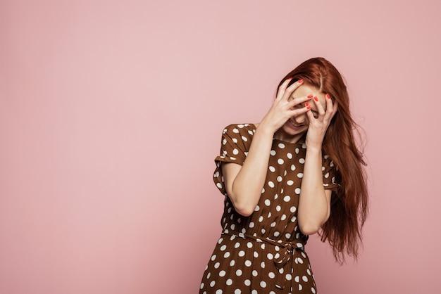 手で頭を抱えている重点を置かれた女性の肖像画。人間の感情、表情のコンセプト。流行色。ピンクの壁で叫んで泣いている感情的な怒っている女性
