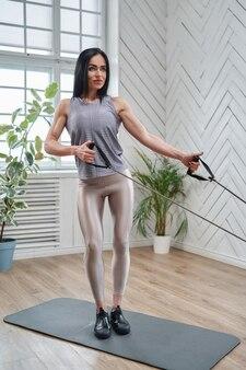 Портрет сильной и спортивной женщины, одетой в спортивную одежду и выполняющей физические упражнения с эластичными лентами в комнате.
