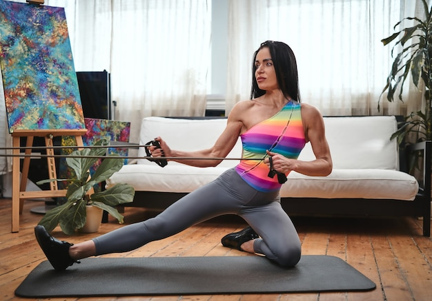 虹色のスポーツウェアを着た強い中年女性の肖像画。彼女は自宅で一人で健康を気にかけています。