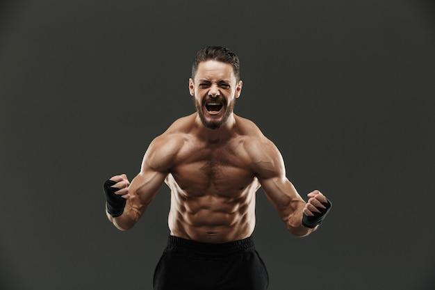 Портрет сильного мускулистого спортсмена празднует