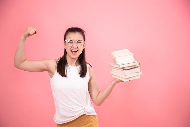 Портрет студентки в очках на розовой стене позирует с книгами в руках. понятие об образовании и увлечениях.