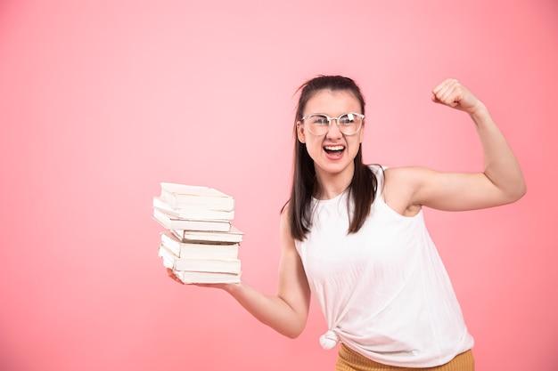 Портрет студентки в очках, позирует с книгами в руках. понятие об образовании и увлечениях.