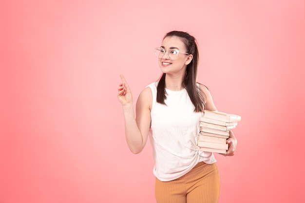 Портрет студентки в очках с книгами в руках. понятие об образовании и увлечениях.
