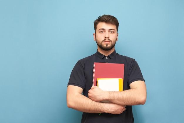 青に立っている暗いシャツを着て、ひげを持つ学生の肖像画