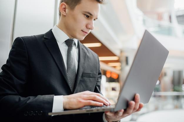 Портрет студента, работающего на ноутбуке, одетого в черный костюм в торговом центре