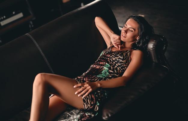 革のソファの上に横たわり、官能的にポーズをとって目を閉じているドレスを着た、巻き毛の見事な美しいブルネットの肖像画。