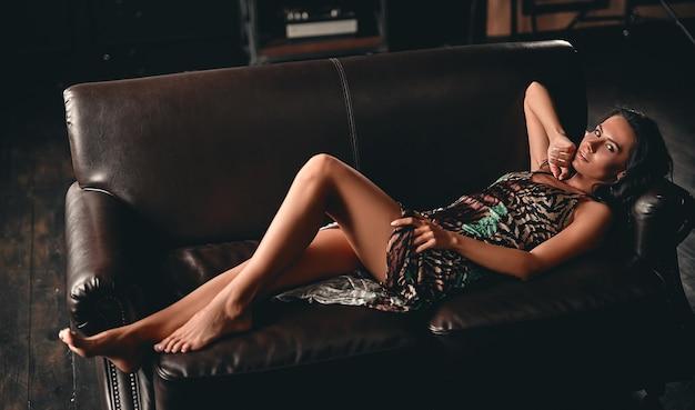 革張りのソファに横になり、官能的にポーズをとるドレスを着て、細長い脚を見せている、巻き毛のある見事な美しいブルネットの肖像画。