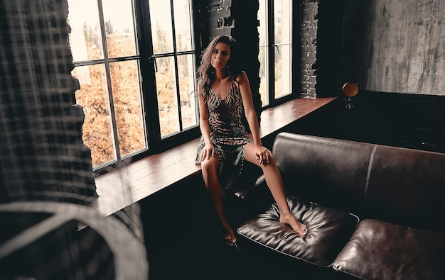 革のソファに寄りかかって、窓辺に座っているドレスを着た巻き毛の見事な美しいブルネットの肖像画。