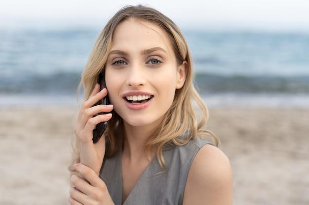 カメラを覗き込んでいるかわいい笑顔で携帯電話で話している見事な金髪の女性の肖像画