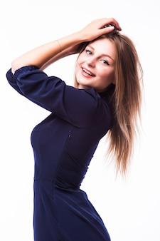 흰색 배경에 고립 된 작은 검은 드레스를 입고 포즈를 취하는 멋진 젊은 여자의 초상화
