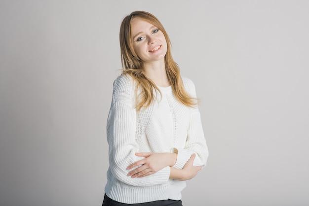 スタジオで白い背景の上のスタイリッシュな笑顔の女の子の肖像画