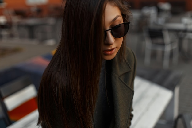屋外カフェに座っている秋の特大のコートとサングラスでスタイリッシュで若いブルネットの少女の肖像画。アウトドアライフスタイル。魅力的な女性。