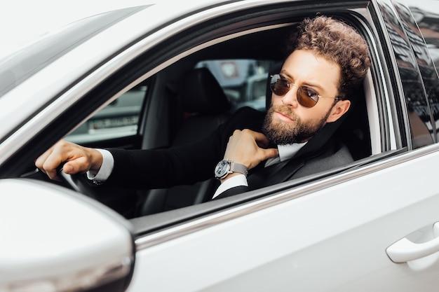흰색 차의 바퀴 뒤에 선글라스를 끼고 수염을 기른 세련된 남자의 초상화, 손에 든 값비싼 시계