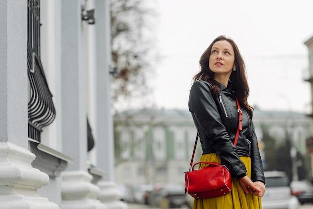 Портрет стильной брюнетки деловой женщины с красной сумочкой