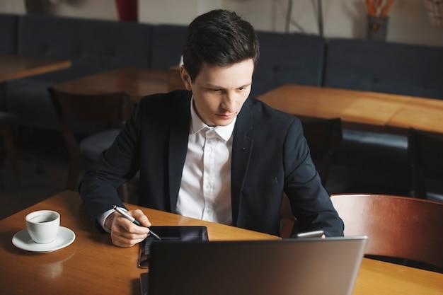 コーヒーショップの彼の机に座っているタブレットで操作しながら彼のラップトップを見ているスーツを着たスタイリッシュな白人男性の肖像画。