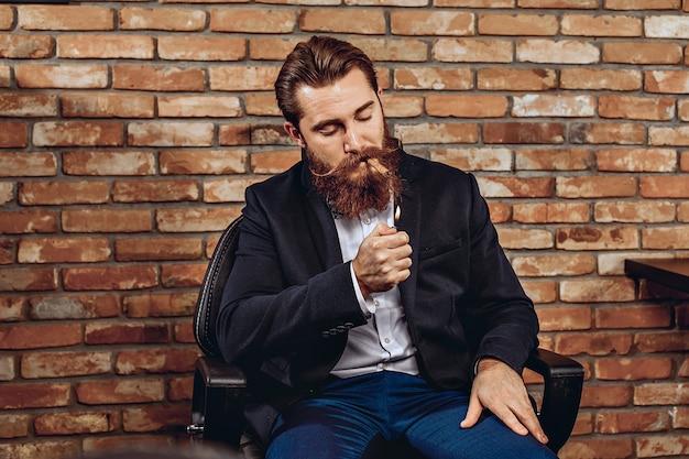 椅子に座って、レンガの壁を背景に葉巻に火をつけるスタイリッシュな勇気あるカリスマ的な男の肖像画。タバコの概念