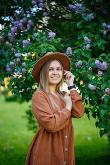 ライラックの背景に茶色の帽子とドレスを着たスタイリッシュな女の子の肖像画。彼女の顔に笑顔でヨーロッパの外観の若い女性