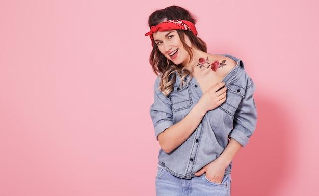 Портрет стильной девушки в джинсовой одежде на розовой стене